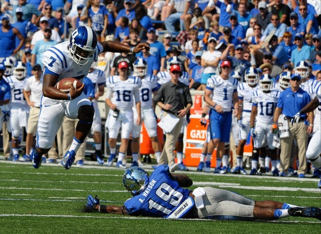 Sep 7, 2013; Memphis, TN, USA; Duke Blue Devils quarterback Anthony Boone (7) leaps over Memphis Tigers defensive back Anthony Watson (19 at Liberty Bowl Memorial. Mandatory Credit: Justin Ford-USA TODAY Sports