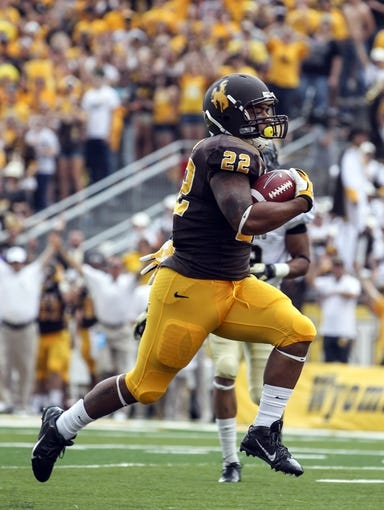 Sep 7, 2013; Laramie, WY, USA; Wyoming Cowboys running back Tedder Easton (22) scores a touchdown against the Idaho Vandals during the second quarter at War Memorial Stadium. Mandatory Credit: Troy Babbitt-USA TODAY Sports