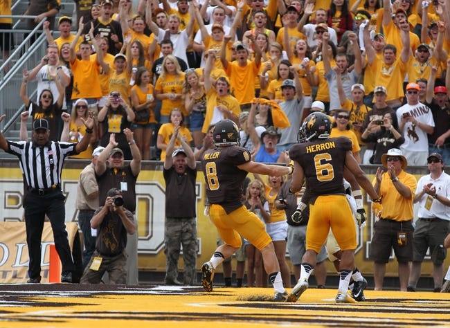 Sep 7, 2013; Laramie, WY, USA; Wyoming Cowboys running back Brandon Miller (8) scores a touchdown against the Idaho Vandals during the second quarter at War Memorial Stadium. Mandatory Credit: Troy Babbitt-USA TODAY Sports