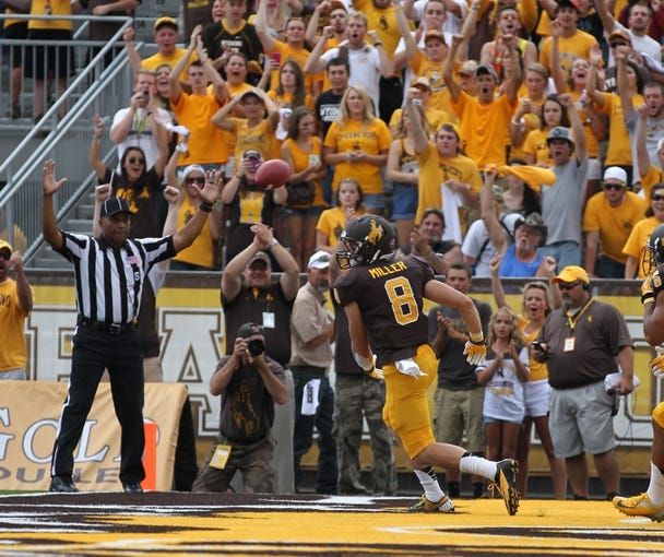 Sep 7, 2013; Laramie, WY, USA; Wyoming Cowboys running back Brandon Miller (8) celebrates after scoring a touchdown against the Idaho Vandals during the second quarter at War Memorial Stadium. Mandatory Credit: Troy Babbitt-USA TODAY Sports