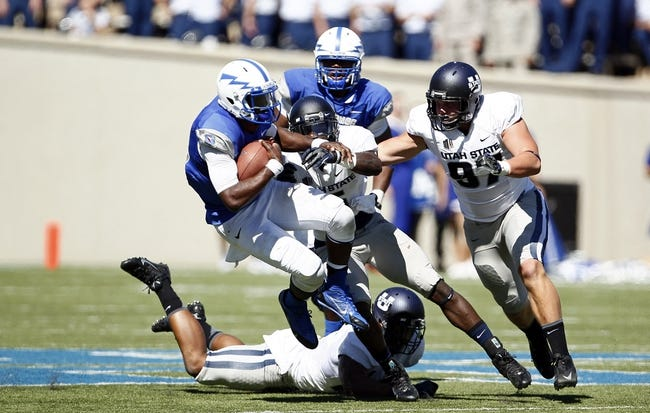 Sep 7, 2013; Colorado Springs, CO, USA; Utah State Aggies safety Maurice Alexander (5) and defensive lineman Jordan Nielsen (97) tackle Air Force Falcons quarterback Jaleel Awini (12) in the second quarter at Falcon Stadium. Mandatory Credit: Isaiah J. Downing-USA TODAY Sports