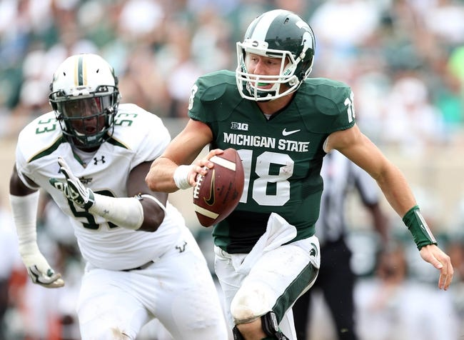 Sep 7, 2013; East Lansing, MI, USA;Michigan State Spartans quarterback Connor Cook (18) scrambles out of the pocket against South Florida Bulls defensive lineman Elkino Watson (53)  during the 2nd half at Spartan Stadium. MSU won 21-6. Mandatory Credit: Mike Carter-USA TODAY Sports