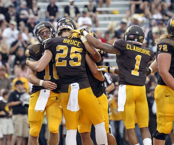 Sep 7, 2013; Laramie, WY, USA; Wyoming Cowboys tight end Spencer Bruce (25) celebrates with teammates Brett Smith (16) and Jalen Claiborne (1) after scoring a touchdown against the Idaho Vandals during the second quarter at War Memorial Stadium. Mandatory Credit: Troy Babbitt-USA TODAY Sports