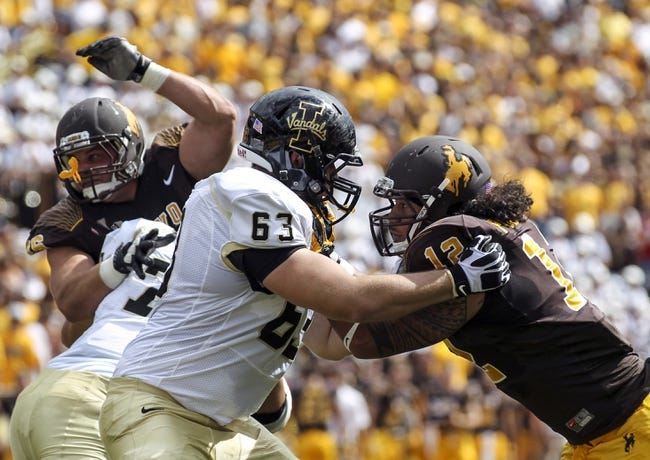 Sep 7, 2013; Laramie, WY, USA; Idaho Vandals offensive lineman Calvin White (63) blocks Wyoming Cowboys linebacker Sonny Puletasi (12) during the first quarter at War Memorial Stadium. Mandatory Credit: Troy Babbitt-USA TODAY Sports
