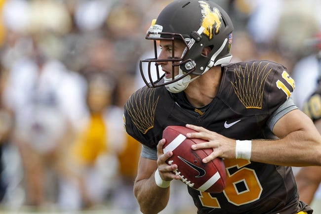 Sep 7, 2013; Laramie, WY, USA; Wyoming Cowboys quarterback Brett Smith (16) rolls out to throw against the Idaho Vandals during the first quarter at War Memorial Stadium. Mandatory Credit: Troy Babbitt-USA TODAY Sports