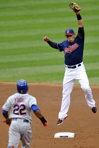 Sep 7, 2013; Cleveland, OH, USA; Cleveland Indians shortstop Asdrubal Cabrera (right) forces out New York Mets left fielder Eric Young Jr. (22) before turning a double play in the first inning at Progressive Field. Mandatory Credit: David Richard-USA TODAY Sports