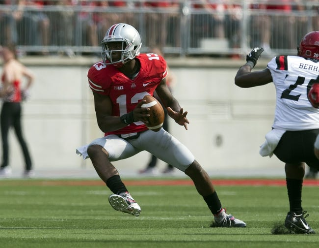 Sep 7, 2013; Columbus, OH, USA; Ohio State Buckeyes quarterback Kenny Guiton (13) cuts back towards open space against the San Diego State Aztecs at Ohio Stadium. Ohio State won the game 42-7. Mandatory Credit: Greg Bartram-USA TODAY Sports