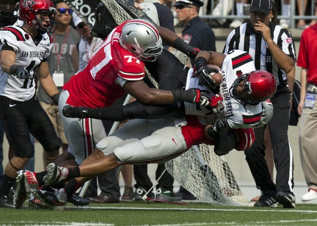 Sep 7, 2013; Columbus, OH, USA; San Diego State Aztecs running back Chase Price (22) is taken down by Ohio State Buckeyes linebacker Ryan Shazier (10) and defensive lineman Michael Hill (77) at Ohio Stadium. Ohio State won the game 42-7. Mandatory Credit: Greg Bartram-USA TODAY Sports
