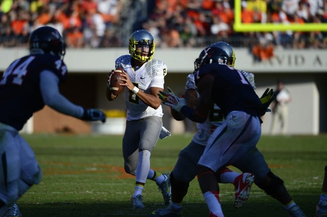 Sep 7, 2013; Charlottesville, VA, USA; Oregon Ducks quarterback Marcus Mariota (8) looks to pass as Virginia Cavaliers linebacker Henry Coley (44) and defensive end Eli Harold (7) defend in the third quarter. The Ducks defeated the Virginia Cavaliers 59-10 at Scott Stadium. Mandatory Credit: Bob Donnan-USA TODAY Sports