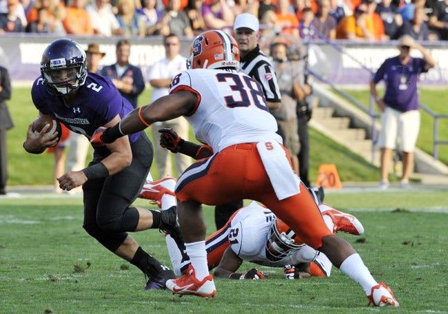 Sep 7, 2013; Evanston, IL, USA; Northwestern Wildcats quarterback Kain Colter (2) tries to run past Syracuse Orange linebacker Cameron Lynch (38) during the first quarter at Ryan Field. Mandatory Credit: David Banks-USA TODAY Sports