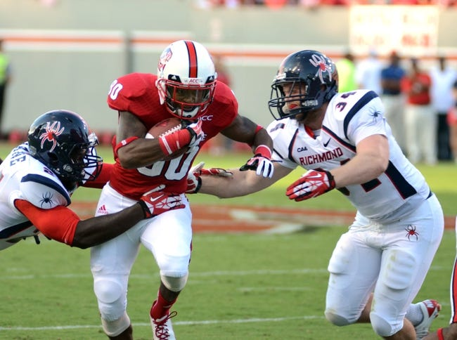 Sep 7, 2013; Raleigh, NC, USA; North Carolina State Wolfpack receiver Bryan Underwood (80) is tackled by Richmond Spiders linebackers Aaron Roane (left) and Eric Wright (34) at Carter Finley Stadium. Mandatory Credit: Rob Kinnan-USA TODAY Sports