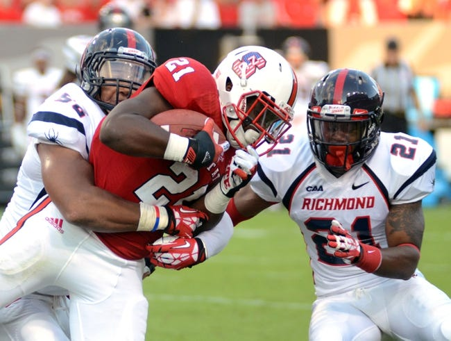 Sep 7, 2013; Raleigh, NC, USA;  North Carolina State Wolfpack running back Matt Dayes (21) is tackled by Richmond Spiders defensive back Justin Grant (21) and defensive tackle Kerry Wynn (56) during the first half  at Carter Finley Stadium. Mandatory Credit: Rob Kinnan-USA TODAY Sports