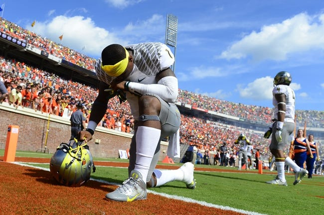 Sep 7, 2013; Charlottesville, VA, USA; Oregon Ducks wide receiver Josh Huff (1) kneels down before the games as safety Erick Dargan (4) is in the background. The Ducks defeated the Virginia Cavaliers 59-10 at Scott Stadium. Mandatory Credit: Bob Donnan-USA TODAY Sports