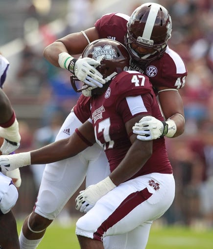 Sep 7, 2013; Starkville, MS, USA; Mississippi State Bulldogs defensive lineman AJ Jefferson (47) celebrates with defensive lineman Ryan Brown (48) after a play against the Alcorn State Braves at Davis Wade Stadium.  The Bulldogs defeated the Braves 51-7. Mandatory Credit: Marvin Gentry-USA TODAY Sports