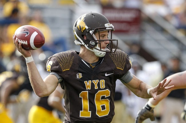 Sep 7, 2013; Laramie, WY, USA; Wyoming Cowboys quarterback Brett Smith (16) rolls out to throw against the Idaho Vandals during the fourth quarter at War Memorial Stadium. The Cowboys defeated the Vandals 42-10. Mandatory Credit: Troy Babbitt-USA TODAY Sports
