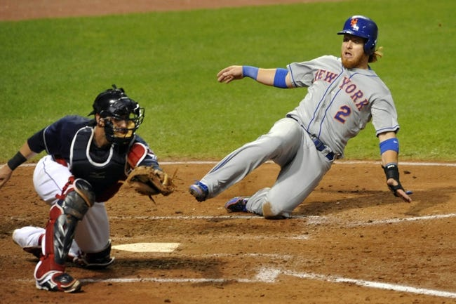 Sep 7, 2013; Cleveland, OH, USA; New York Mets third baseman Justin Turner (2) slides into home plate while scoring before a tag by Cleveland Indians catcher Yan Gomes (10) in the sixth inning at Progressive Field. Mandatory Credit: David Richard-USA TODAY Sports
