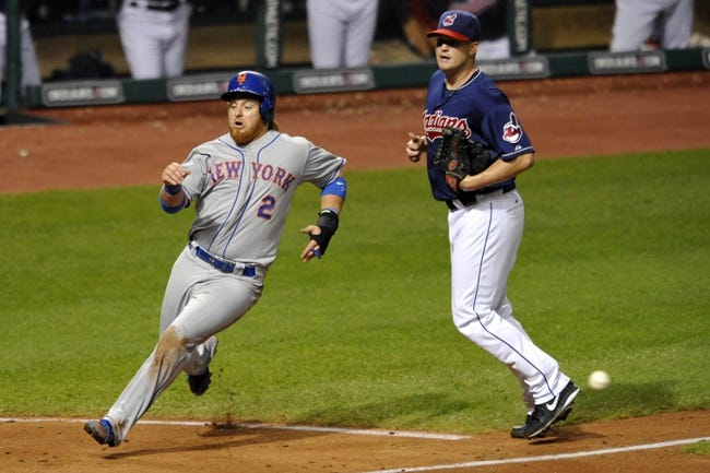 Sep 7, 2013; Cleveland, OH, USA; New York Mets third baseman Justin Turner (2) runs past Cleveland Indians relief pitcher Vinnie Pestano (52) while scoring in the sixth inning at Progressive Field. Mandatory Credit: David Richard-USA TODAY Sports