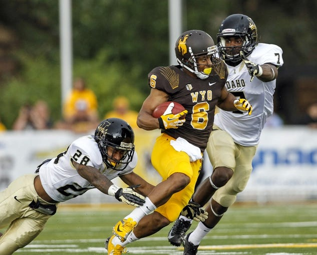 Sep 7, 2013; Laramie, WY, USA; Wyoming Cowboys wide receiver Robert Herron (6) runs against Idaho Vandals safety Trey Williams (7) and cornerback Solomon Dixon (28) during the third quarter at War Memorial Stadium. The Cowboys defeated the Vandals 42-10. Mandatory Credit: Troy Babbitt-USA TODAY Sports