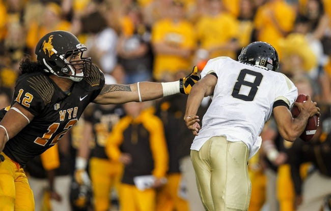 Sep 7, 2013; Laramie, WY, USA; Wyoming Cowboys linebacker Sonny Puletasi (12) reaches for Idaho Vandals quarterback Joshua McCain (8) during the third quarter at War Memorial Stadium. The Cowboys defeated the Vandals 42-10. Mandatory Credit: Troy Babbitt-USA TODAY Sports
