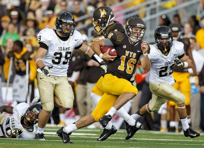 Sep 7, 2013; Laramie, WY, USA; Wyoming Cowboys quarterback Brett Smith (16) runs against the Idaho Vandals during the third quarter at War Memorial Stadium. The Cowboys defeated the Vandals 42-10. Mandatory Credit: Troy Babbitt-USA TODAY Sports