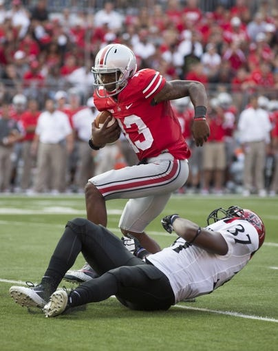 Sep 7, 2013; Columbus, OH, USA; Ohio State Buckeyes quarterback Kenny Guiton (13) spins away from a tackle attempted by San Diego State Aztecs linebacker Vaness Harris (37) at Ohio Stadium. Ohio State won the game 42-7. Mandatory Credit: Greg Bartram-USA TODAY Sports