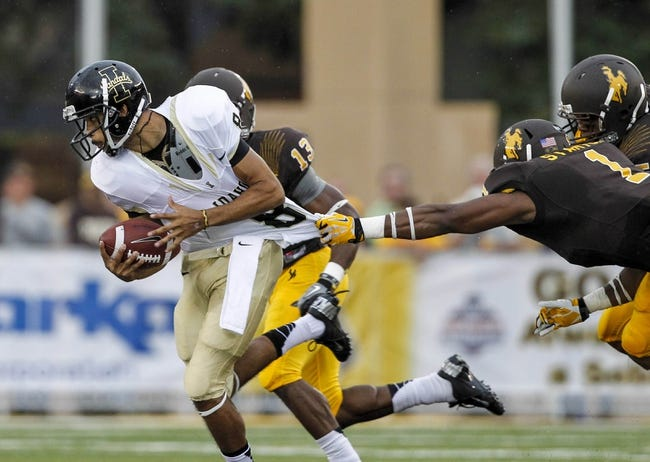 Sep 7, 2013; Laramie, WY, USA; Idaho Vandals quarterback Joshua McCain (8) tries to pull away from Wyoming Cowboys linebacker Jordan Stanton (1)during the second quarter at War Memorial Stadium. The Cowboys defeated the Vandals 42-10. Mandatory Credit: Troy Babbitt-USA TODAY Sports
