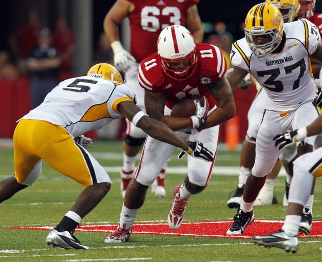 Sep 7, 2013; Lincoln, NE, USA; Nebraska Cornhuskers running back Cethan Carter (11) runs against Southern Mississippi Golden Eagles defenders Jerrion Johnson (5) and Alan Howze (37) in the third quarter at Memorial Stadium. Mandatory Credit: Bruce Thorson-USA TODAY Sports