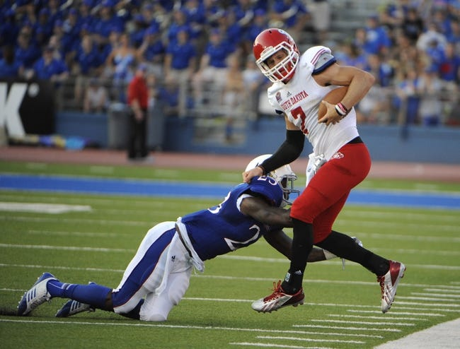 Sep 7, 2013; Lawrence, KS, USA; South Dakota Coyotes quarterback Josh Vander Maten (7) is pushed out of bounds by Kansas Jayhawks safety Dexter Linton (23) in the first half at Memorial Stadium. Mandatory Credit: John Rieger-USA TODAY Sports