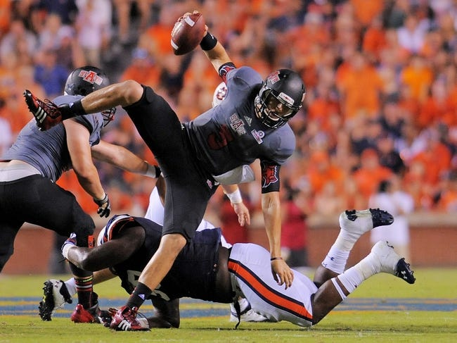 Sep 7, 2013; Auburn, AL, USA; Arkansas State Red Wolves quarterback Adam Kennedy (5) tries to run the ball and is tripped up by Auburn Tigers defensive tackle Ben Bradley (50) at Jordan Hare Stadium. Mandatory Credit: Shanna Lockwood-USA TODAY Sports
