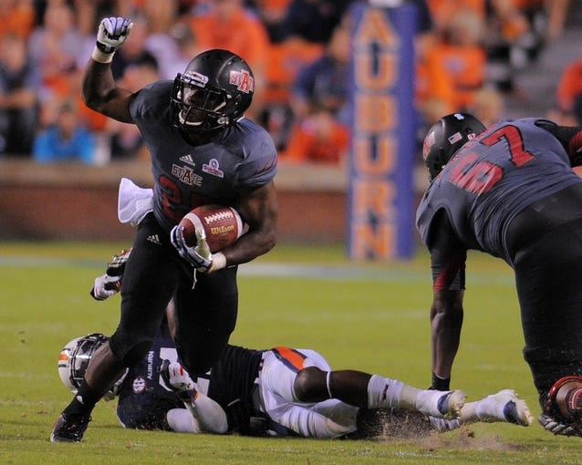 Sep 7, 2013; Auburn, AL, USA; Arkansas State Red Wolves running back David Oku (25) makes it past Auburn Tigers defense during the first half at Jordan Hare Stadium. Mandatory Credit: Shanna Lockwood-USA TODAY Sports