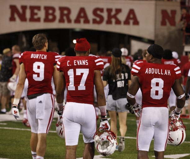 Sep 7, 2013; Lincoln, NE, USA; Nebraska Cornhuskers players Sam Burtch (9), Ciante Evans (17) and Ameer Abdullah (8) leave the field after defeating Southern Mississippi Golden Eagles at Memorial Stadium. Nebraska won 56-13. Mandatory Credit: Bruce Thorson-USA TODAY Sports