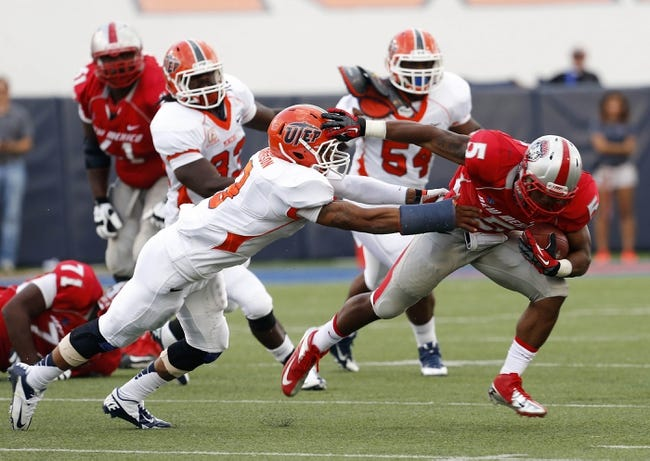 Sep 7, 2013; El Paso, TX, USA; New Mexico Lobos running back Kasey Carrier (5) tries to break a tackle from UTEP Miners defensive back Traun Roberson (3) during the first half at Sun Bowl Stadium. Mandatory Credit: Ivan Pierre Aguirre-USA TODAY Sports