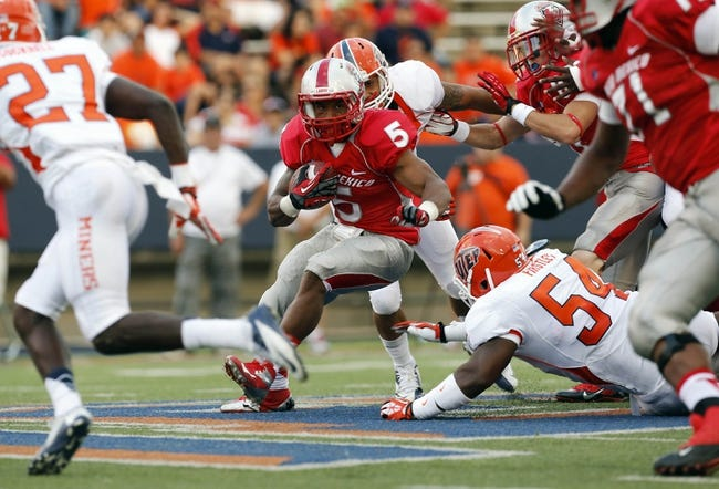 Sep 7, 2013; El Paso, TX, USA; New Mexico Lobos running back Kasey Carrier (5) tries to break free from the UTEP Miners defense during the first half at Sun Bowl Stadium. Mandatory Credit: Ivan Pierre Aguirre-USA TODAY Sports