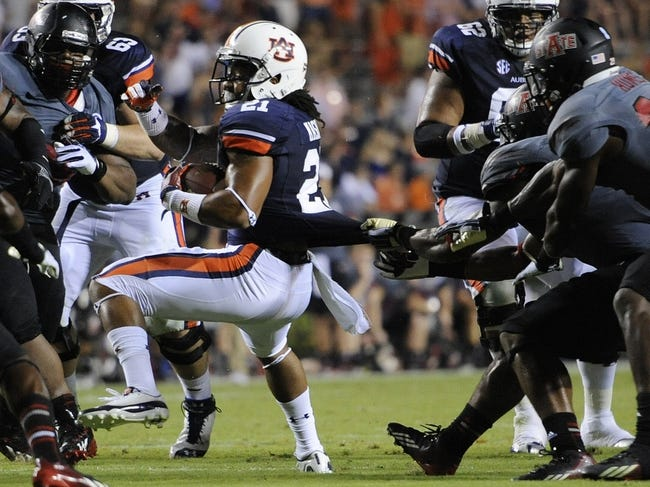 Sep 7, 2013; Auburn, AL, USA; Auburn Tigers running back Tre Mason (21) is brought down by Arkansas State Red Wolves defense during the second half at Jordan Hare Stadium. Mandatory Credit: Shanna Lockwood-USA TODAY Sports