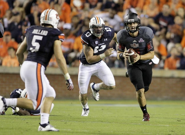 Sep 7, 2013; Auburn, AL, USA; Arkansas State Red Wolves quarterback Adam Kennedy (5) avoids Auburn Tiger defenders Jake Holland (5) and Craig Sanders (13) during the second half at Jordan Hare Stadium.  Mandatory Credit: John Reed-USA TODAY Sports