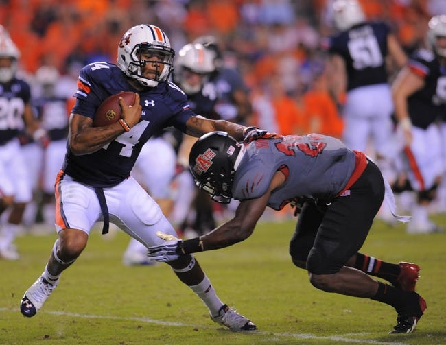 Sep 7, 2013; Auburn, AL, USA; Auburn Tigers quarterback Nick Marshall (14) tries to elude the defense of Arkansas State Red Wolves running back Kendrick Daniels (29) at Jordan Hare Stadium. Mandatory Credit: Shanna Lockwood-USA TODAY Sports