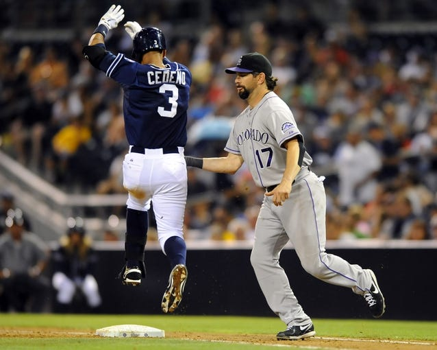 Sep 7, 2013; San Diego, CA, USA; Colorado Rockies first baseman Todd Helton (17) tags out San Diego Padres shortstop Ronny Cedeno (3) after being pulled off the bag for the final out of the sixth inning at Petco Park. Mandatory Credit: Christopher Hanewinckel-USA TODAY Sports