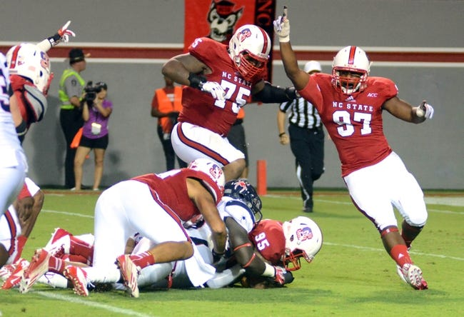 Sep 7, 2013; Raleigh, NC, USA;   North Carolina State Wolfpack defensive end Forrest West (97) celebrates as teammate Art Norman (95) recovers a fumble against the Richmond Spiders at Carter Finley Stadium.  North Carolina State won 23-21. Mandatory Credit: Rob Kinnan-USA TODAY Sports