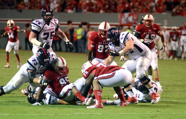 Sep 7, 2013; Raleigh, NC, USA;   North Carolina State Wolfpack defensive tackle T.Y. McGill (75) bends down to recover a Richmond Spiders fumble during the second half at Carter Finley Stadium. North Carolina State won 23-21. Mandatory Credit: Rob Kinnan-USA TODAY Sports