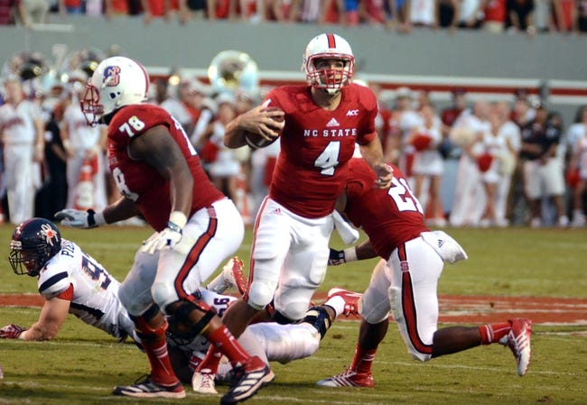 Sep 7, 2013; Raleigh, NC, USA; North Carolina State Wolfpack quarterback Pete Thomas (4) breaks a tackle and scrambles during the second half against the Richmond Spiders at Carter Finley Stadium.  North Carolina State won 23-21. Mandatory Credit: Rob Kinnan-USA TODAY Sports