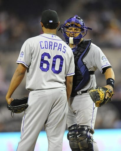 Sep 7, 2013; San Diego, CA, USA; Colorado Rockies catcher Yorvit Torrealba (8) talks with relief pitcher Manny Corpas (60) during the seventh inning against the San Diego Padres at Petco Park. Mandatory Credit: Christopher Hanewinckel-USA TODAY Sports
