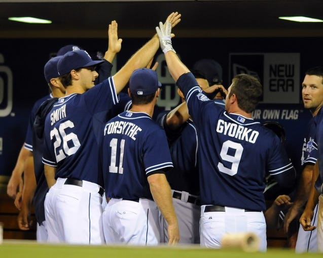 Sep 7, 2013; San Diego, CA, USA; San Diego Padres second baseman Jedd Gyorko (9) is congratulated by teammates after a go-ahead home run during the eighth inning against the Colorado Rockies at Petco Park. Mandatory Credit: Christopher Hanewinckel-USA TODAY Sports