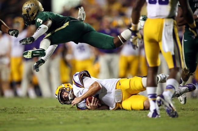 Sep 7, 2013; Baton Rouge, LA, USA; UAB Blazers cornerback Lamarcus Farmer (3) leaps over LSU Tigers quarterback Zach Mettenberger (8) in the second half at Tiger Stadium. LSU defeated UAB 56-17. Mandatory Credit: Crystal LoGiudice-USA TODAY Sports