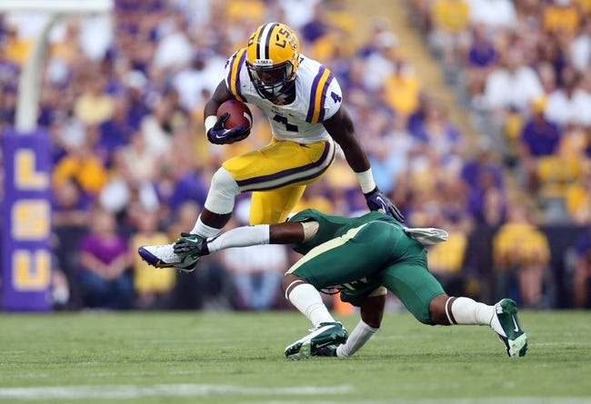 Sep 7, 2013; Baton Rouge, LA, USA; LSU Tigers quarterback Rob Bolden (1) leaps over UAB Blazers cornerback Lamarcus Farmer (3) as he carries the ball in the first quarter at Tiger Stadium. LSU defeated UAB 56-17. Mandatory Credit: Crystal LoGiudice-USA TODAY Sports