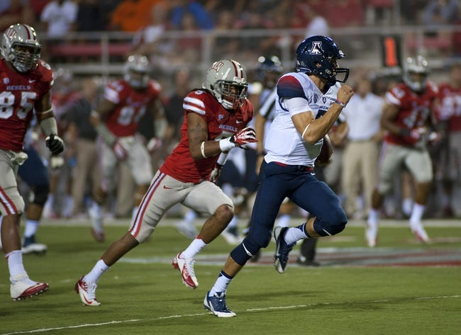Sep 7, 2013; Las Vegas, NV, USA; Arizona Wildcats quarterback B.J. Denker sprints away from the UNLV defense to score a touchdown during an NCAA football game at Sam Boyd Stadium. Mandatory Credit: Stephen R. Sylvanie-USA TODAY Sports