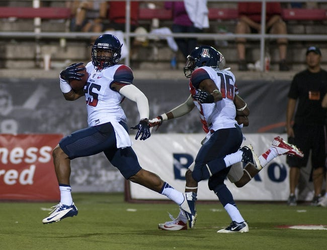 Sep 7, 2013; Las Vegas, NV, USA; Arizona Wildcats runningback Ka'Deem Carey cruises away from the UNLV Rebel defense to score the second of two first half rushing touchdowns at Sam Boyd Stadium. Mandatory Credit: Stephen R. Sylvanie-USA TODAY Sports