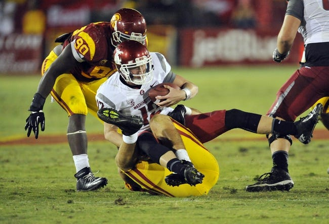 September 7, 2013; Los Angeles, CA, USA; Washington State Cougars quarterback Connor Halliday (12) is brought down by Southern California Trojans linebacker Morgan Breslin (91) during the second half at the Los Angeles Memorial Coliseum. Mandatory Credit: Gary A. Vasquez-USA TODAY Sports