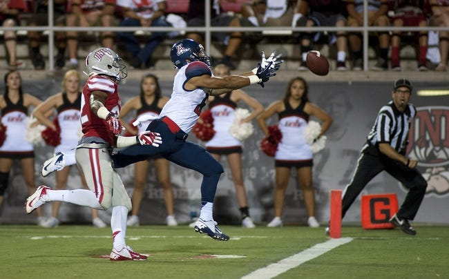 Sep 7, 2013; Las Vegas, NV, USA; Arizona Wildcats wide receiver Nate Phillips reaches for a ball near the goal line with UNLV Rebels defensiveback Mike Horsey on defense during an NCAA football game at Sam Boyd Stadium. Arizona won the game 58-13. Mandatory Credit: Stephen R. Sylvanie-USA TODAY Sports