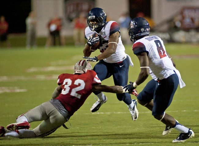 Sep 7, 2013; Las Vegas, NV, USA; Arizona Wildcats runningback Jared Baker leaps through the tackle of UNLV Rebels defensive back Mike Horsey during an NCAA football game at at Sam Boyd Stadium. The Wildcats won the game 58-13. Mandatory Credit: Stephen R. Sylvanie-USA TODAY Sports