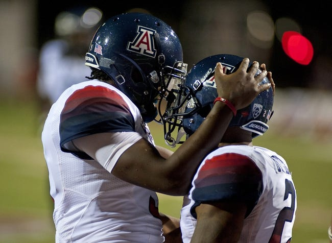 Sep 7, 2013; Las Vegas, NV, USA; Arizona Wildcats running back Kylan Butler (right) celebrates with quarterback Javelle Allen after scoring a touchdown against the UNLV Rebels at Sam Boyd Stadium. Arizona won the game 58-13. Mandatory Credit: Stephen R. Sylvanie-USA TODAY Sports